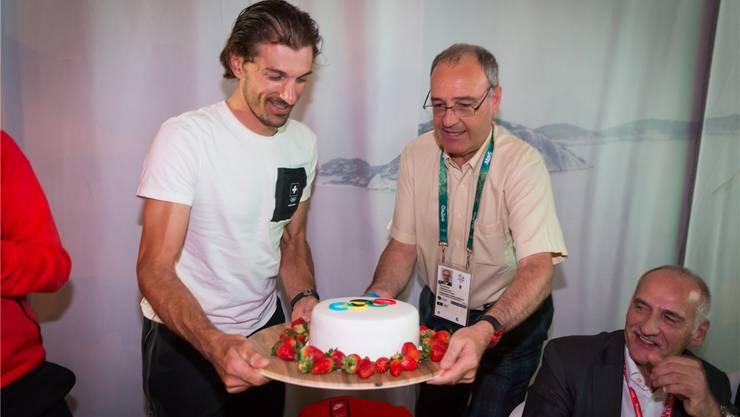 Süsse Überraschung für den Olympiasieger: Bundesrat Guy Parmelin überreicht Fabian Cancellara einen Spezialkuchen.
