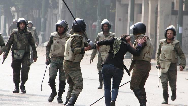 Ein Polizist holt zum Schlag auf eine Demonstrantin aus.