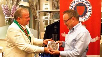 Gilbert Ernst (links) überreicht Thomas Rhiner die Plakette.