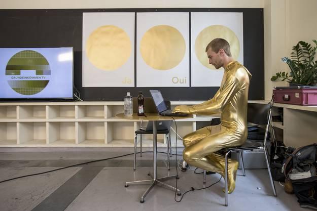 """Der """"Golden Boy"""" Kim-Fabian von Dall'Armi sitzt am Computer, am Abstimmungsfest der Initianten der Grundeinkommensinitiative."""