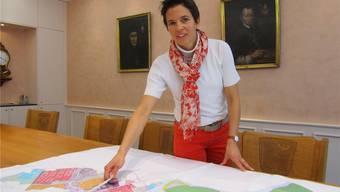 Gemeinderätin Mirjam Egloff zeigt auf dem Zonenplan im Ratssaal, wo die künftigen Einkaufszonen gefördert werden.