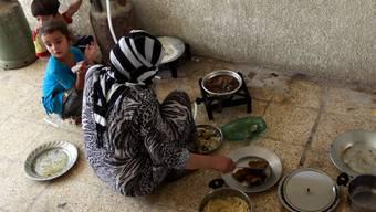 Eine aus Mossul geflüchtete Frau kocht in prekären Verhältnissen