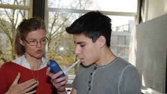 Unter Aufsicht von Katharina Hug bläst Dario in das Messgerät. Er ist aus Überzeugung Nichtraucher.