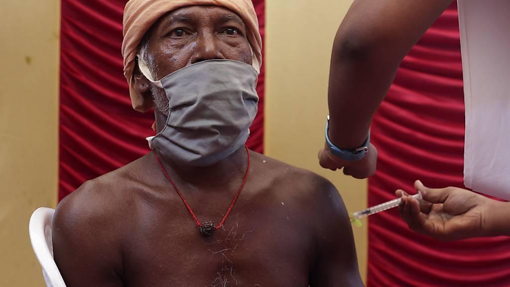 dpatopbilder - Ein Mitarbeiter des indischen Gesundheitswesens impft einen Mann. Angesichts deutlich sinkender Infektionszahlen wagen die Millionenstädte Delhi und Mumbai zusammen mit weiteren Regionen nun erste Lockerungen. Foto: Sri Loganathan/ZUMA Wire/dpa