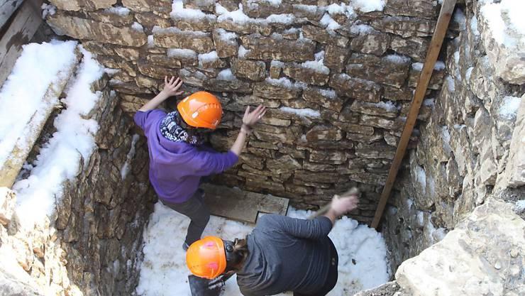 Forschende treten den eingefüllten Schnee im römischen Kühlschrank von Augusta Raurica fest. (Archivbild)