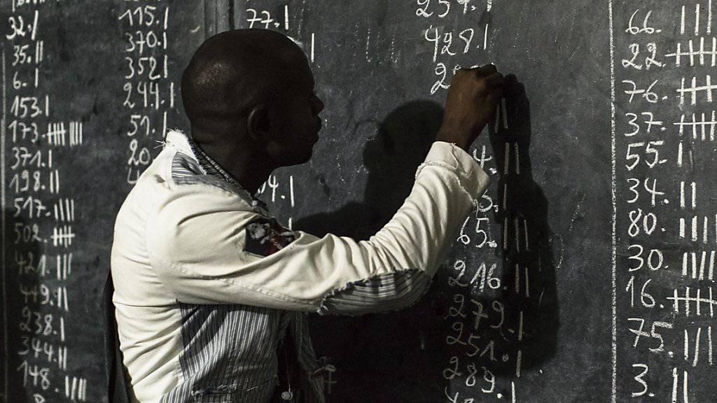 Ein Wahlmitarbeiter bei der Stimmenauswertung in einem Urnenlokal in Kinshasa. (Archivbild)