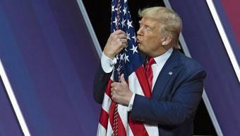 Präsident Trump inszeniert sich als Beschützer der Nation - und küsst die US-Flagge an einer Wahlkampfrallye am Wochenende in Maryland.