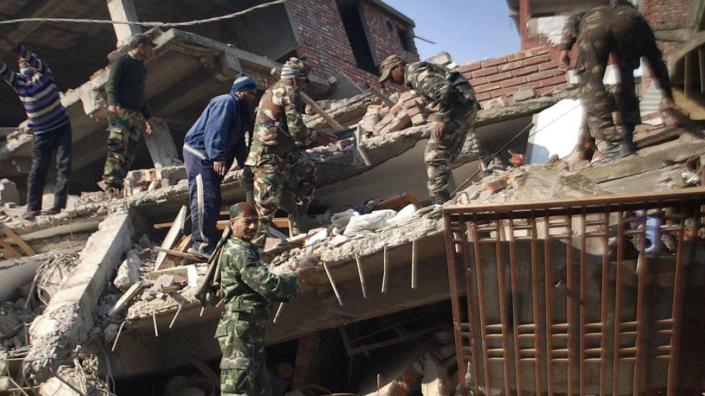 Indische Soldaten und lokale Hilfskräfte bei der Räumung von Erdbebentrümmern in Imphal