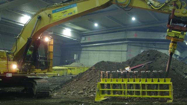 Ein Bagger deponiert Bodenproben im Proberohrgestell in der Sondermülldeponie Kölliken (Bild: SMDK, Archiv)