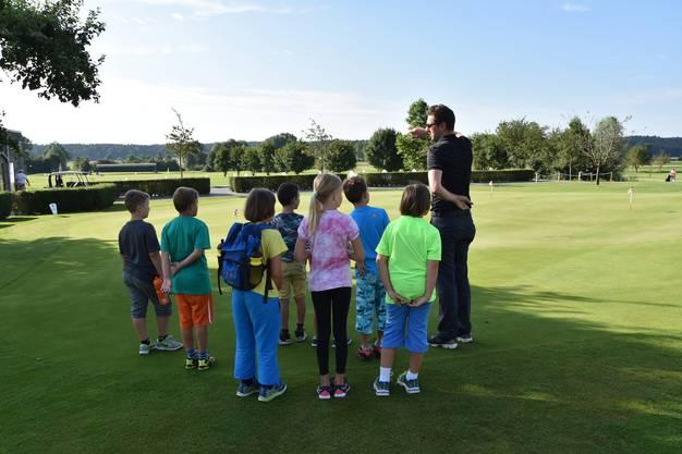 Steven Walther zeigt den Ferienpässlern die Weiten des Golfplatzes
