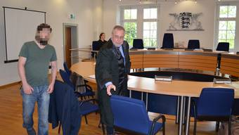 Der Angeklagte und sein Verteidiger nehmen im Gerichtssaal Platz.