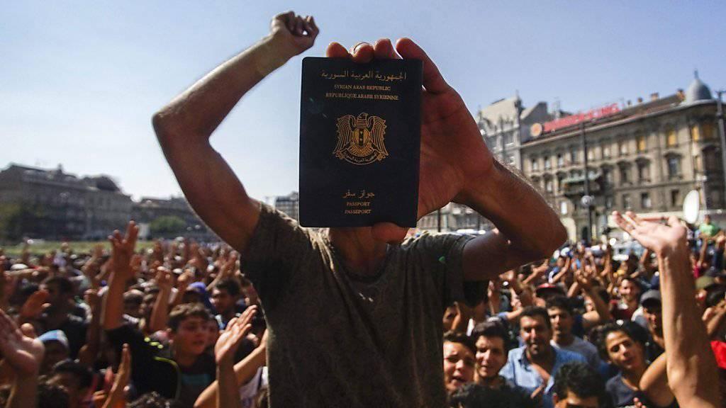 Ein Syrer zeigt seinen Pass, während er vor dem Budapester Ostbahnhof für seine Weiterreise protestiert. Beobachter zählten bis zu 3000 Flüchtlinge, die vor dem Gebäude oder im U-Bahn-Komplex um dem Bahnhof die Nacht verbracht hatten.