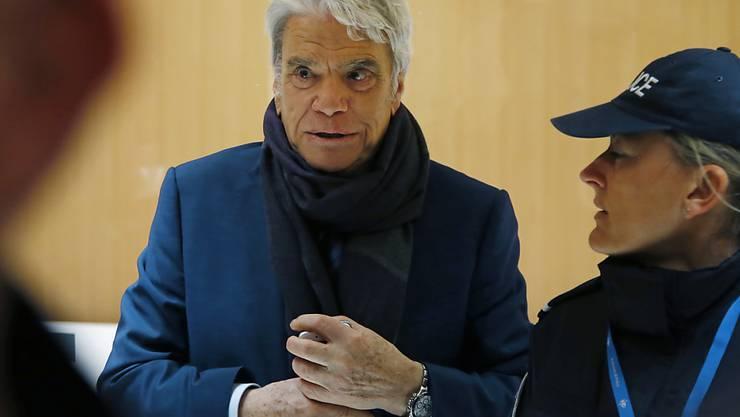 Im Prozess gegen den früheren Adidas-Eigner und Ex-Minister Bernard Tapie, hier eskortiert von einer Polizistin, fordert die Staatsanwaltschaft in Paris fünf Jahre Haft. (Archivbild)