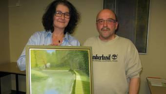 Das frischgebackene Ehrenmitglied Romeo Gorza erhält aus den Händen von Vorstandsmitglied Silvia Aerni ein Bild vom Weiher im Trimbacher «Graben».