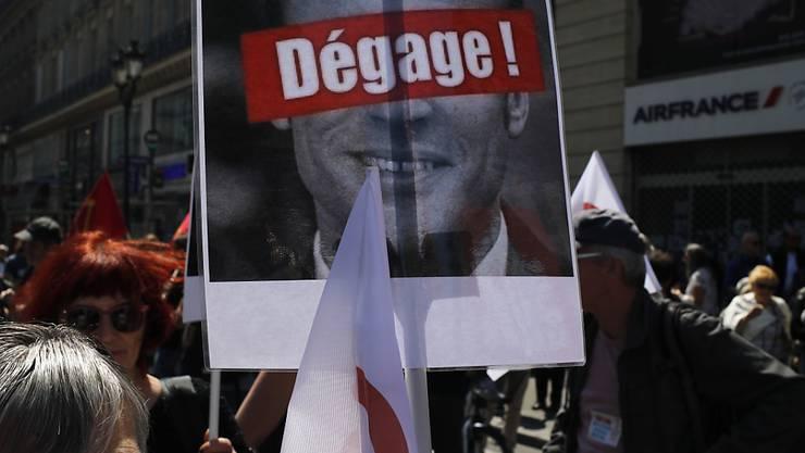 """""""Hau ab!"""" steht auf einem Protestplakat mit dem Konterfei von Präsident Emmanuel Macron, das Demonstranten am Samstag in Paris tragen."""