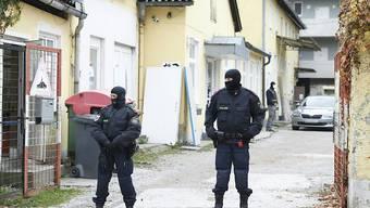 Zwei Polizisten stehen in einer Einfahrt an einem Einsatzort der Operation «Luxor» in Graz. Foto: Erwin Scheriau/APA/dpa - ACHTUNG: Die Kfz-Kennzeichen wurden aus persönlichkeitsrechtlichen Gründen gepixelt.