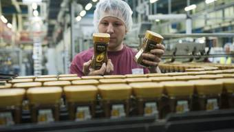 Ein Fabrikarbeiter steht vor einem Fliessband mit Nescafé-Gläsern