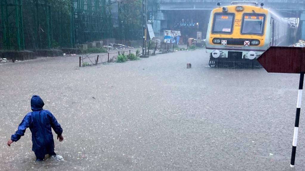 Ein Mann bahnt sich während heftiger Regenfälle seinen Weg über die überfluteten Gleise eines Bahnhofs.