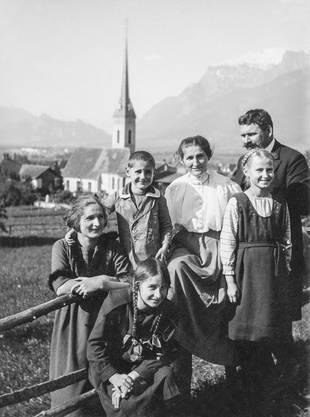 Greti Caprez mit ihren Eltern und ihren Geschwistern in Igis (GR). In der Kirche im Hintergrund war ihr Vater Pfarrer. (Bildquelle: Nachlass Greti Caprez)