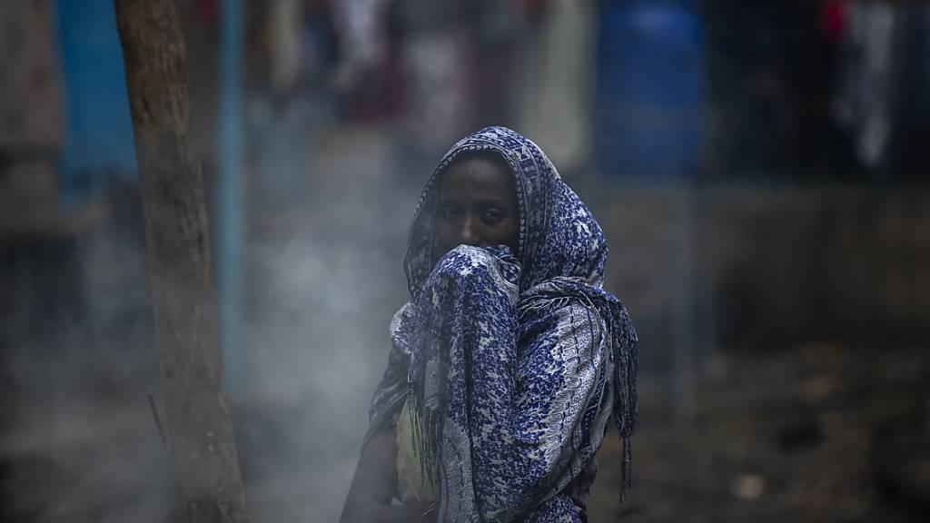 ARCHIV - Eine Frau schützt ihr Gesicht vor Rauch, während sie in einer Schule ein Fladenbrot zubereitet. Der andauernde Konflikt in der Region Tigray hat bereits Hunderttausende Menschen in die Flucht getrieben und große Zerstörung angerichtet. Foto: Ben Curtis/AP/dpa