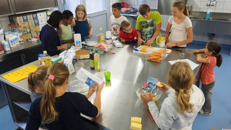 Die Kinder lernen, wie man eine brasilianische Rüeblitorte und Käsebällchen herstellt. Bruno Kissling
