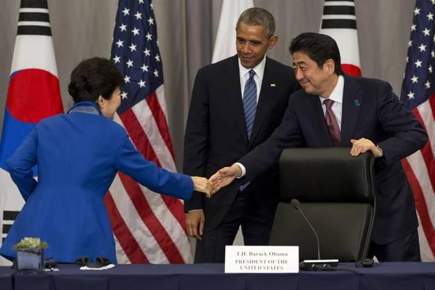 Südkoreas Präsident Paark Geun-hye und Japams Premier Abe schütterln sich in Anwesenheit von Obama die Hand. Dies am Gipfel für Nukleare Sicherheit.