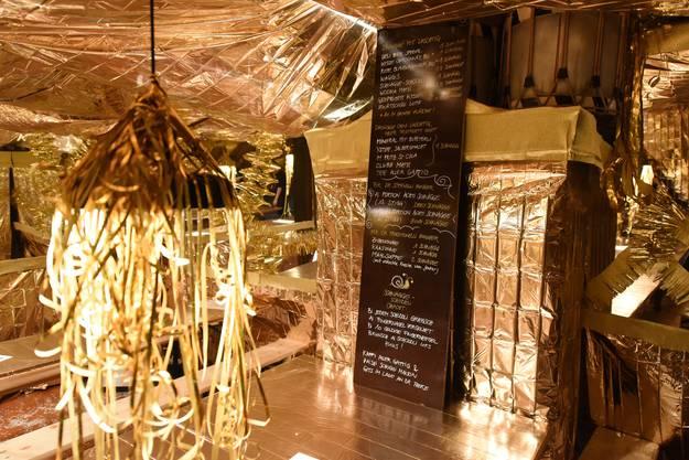 Der Keller ist liebevoll dekoriert, die Wände sind mit goldigen Rettungsdecken abgedeckt.