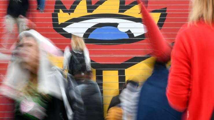 ARCHIV - Besucher gehen in der Glashalle über die Treppe mit dem Logo der Leipziger Buchmesse. Die Leipziger Buchmesse verschiebt ihren Termin im nächsten Jahr vom März auf Ende Mai. Foto: Jens Kalaene/dpa-Zentralbild/dpa