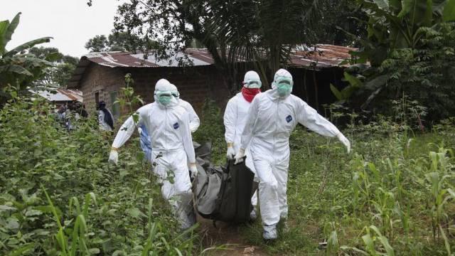 Liberianische Pfleger tragen die Leiche eines Ebola-Opfers weg