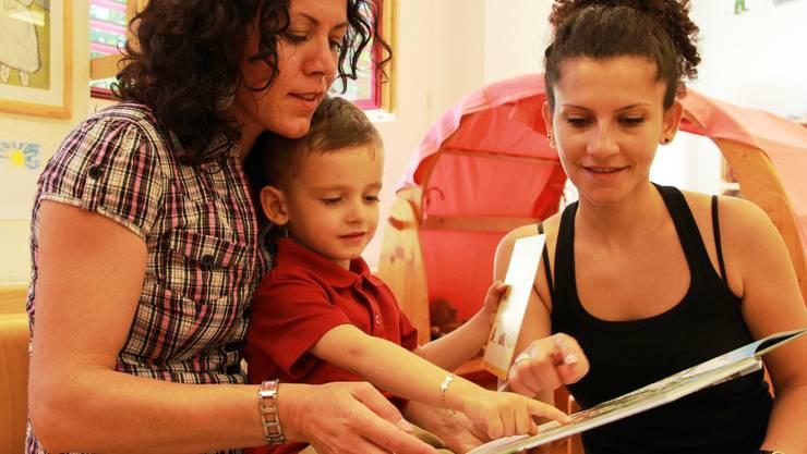Fexhrije Gashi (l.) liest mit Fatbardha Nuredinis Sohn Jon ein Buch.  cnd