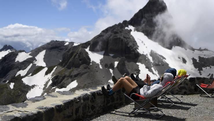 Wanderer sonnen sich bei einer Berghütte im Kanton Wallis.
