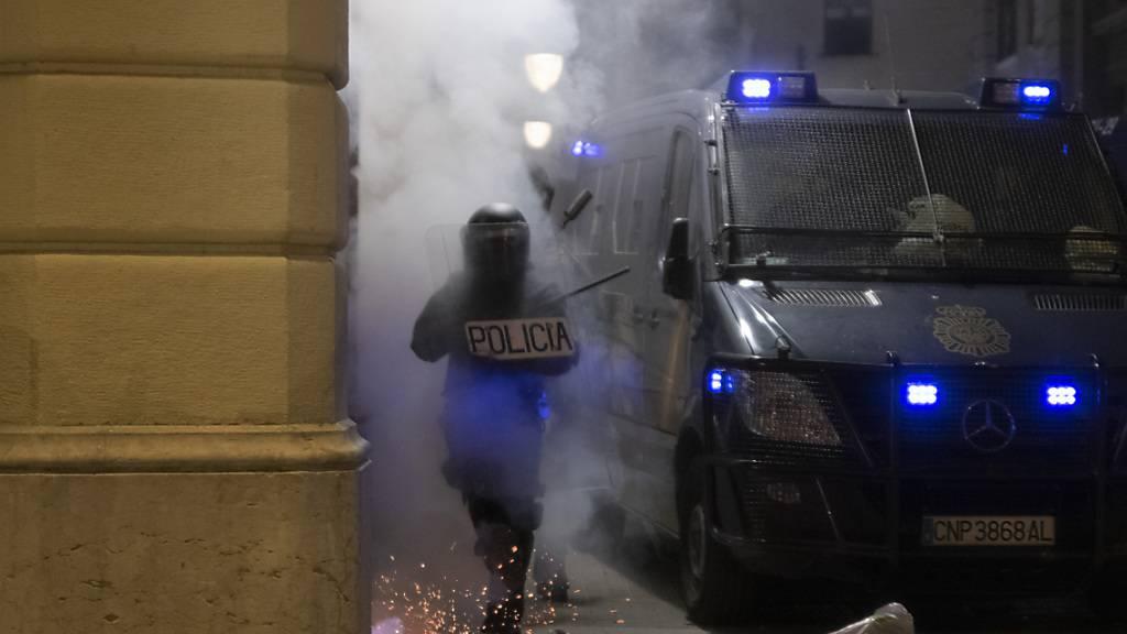 Ein Polizist läuft bei Ausschreitungen wegen der Inhaftierung des Rappers Hasél durch Rauch.  Am Wochenende gab es wieder jede Nacht Ausschreitungen. Foto: Lorena Sopêna I Lòpez/EUROPA PRESS/dpa