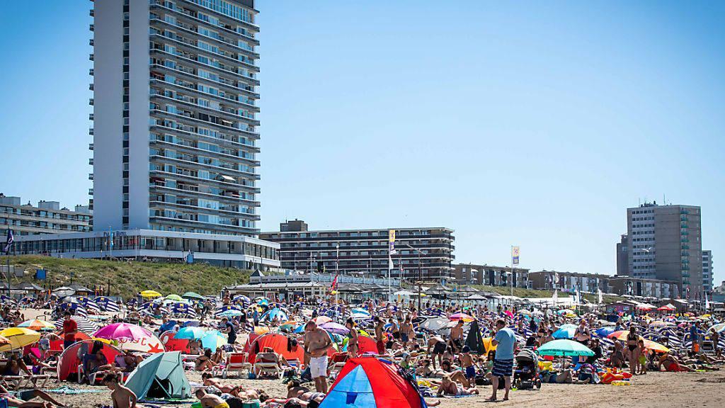"""Zahlreiche Menschen genießen das heiße Wetter am Strand nahe dem Bahnhof Zandvoort. Foto: «laurens Bosch»,""""laurens Bosch L/ANP/dpa"""