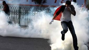 Die Polizei schlägt einen Demonstranten mit Tränengas in die Flucht