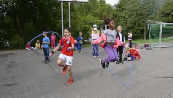 Kinder beim Seilspringen am Sporttag.