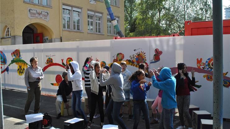 Eine Klasse der Schule Neuenhof führt vor der frisch bemalten Bauumzäunung anstelle eines Spatenstichs einen Schneckenrap auf. LVO