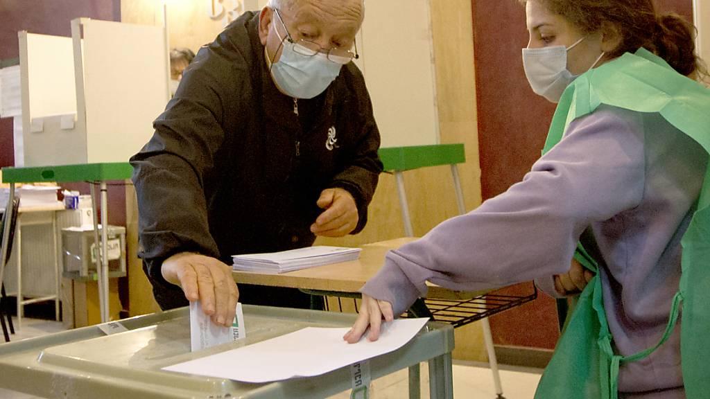 Ein Mann wirft seinen Stimmzettel in eine Wahlurne in einem Wahllokal während der Kommunalwahlen. In der Südkaukasus-Republik Georgien wächst nach der Festnahme des früheren Präsidenten M. Saakaschwili die Sorge vor neuen innenpolitischen Spannungen. Foto: Shakh Aivazov/AP/dpa