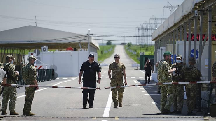Ein Kontrollpunkt zwischen dem von der ukrainischen Regierung und dem von Rebellen kontrollierten Gebiet nahe von Donezk. Im Kriegsgebiet tritt eine Minute nach Mitternacht (23.01 Uhr MESZ) die Vereinbarung über die Waffenruhe in Kraft. (Archivbild vom Juni)