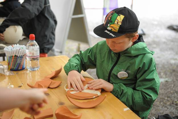 Auf der Kindergrabung können die Kinder Fundobjekte entdecken und ausgraben, um diese anschliessend mit Hilfe von Archäologinnen und Archäologen zu bestimmen und zu dokumentieren.