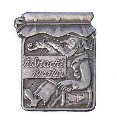 Die meisten Plaketten wurden während des Zweiten Weltkriegs aus Zink hergestellt, weil Kupfer knapp und teuer war. Die «Ygmachti Fasnacht» im Konfiglas spielte darauf an, dass die Strassenfasnacht während des Kriegs verboten war und der Fasnächtler ...