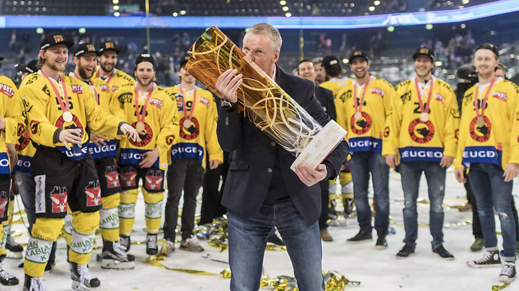 Der Berner Cheftrainer Kari Jalonen küsst den Meisterpokal und feiert in Zug mit seiner Mannschaft