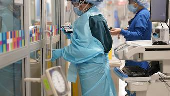 """Zwei Medizinerinnen in Schutzkleidung arbeiten auf einer Station im Krankenhaus """"Bellevue Hospital"""". Die Krankenhäuser des öffentlichen Gesundheits- und Krankenhaussystems der Stadt New York haben ihre Ausrüstung aufgerüstet, um sich auf eine mögliche zweite Welle der Corona-Pademie vorzubereiten. Foto: Seth Wenig/AP/dpa"""
