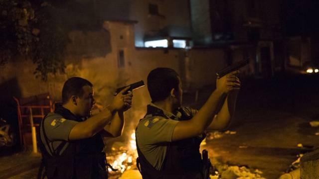 Polizisten patrouillieren neben brennenden Barrikaden in Rio