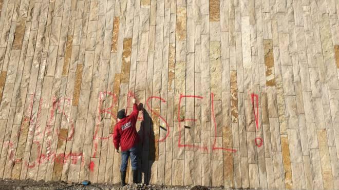 Der Angestellte einer Basler Reinigungsfirma entfernt eine Sprayerei an der Mauer des Elsässerrheinwegs im St. Johann. Foto: ZVG