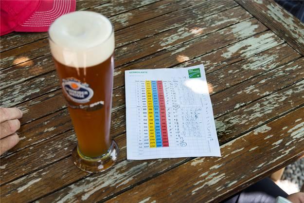 Bei einem Bier kann die Skorekarte studiert werden