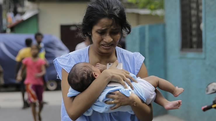Eine Frau, die in der Nähe der St.-Antonius-Kirche in Colombo lebt, rennt mit ihrem Kind im Arm weg, nachdem die Polizei in einem Auto einen Sprengsatz gefunden hat.
