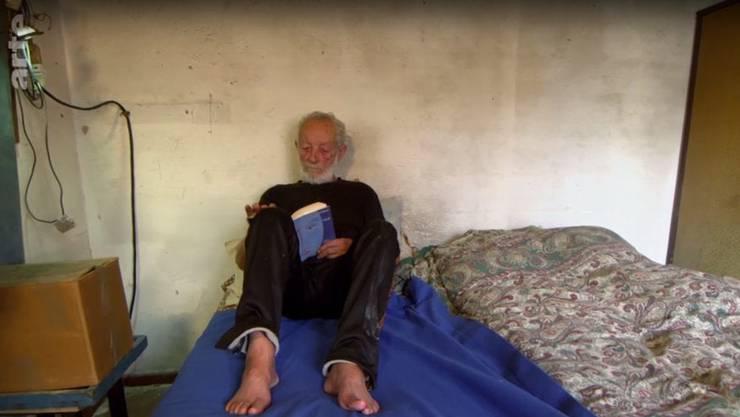 Langweilig wird es Mauro Morandi auf seiner Insel nie. Wenn er gerade nichts zu tun hat, dann liest er – manchmal auch wochenlang. (Screenshot: arte.tv )