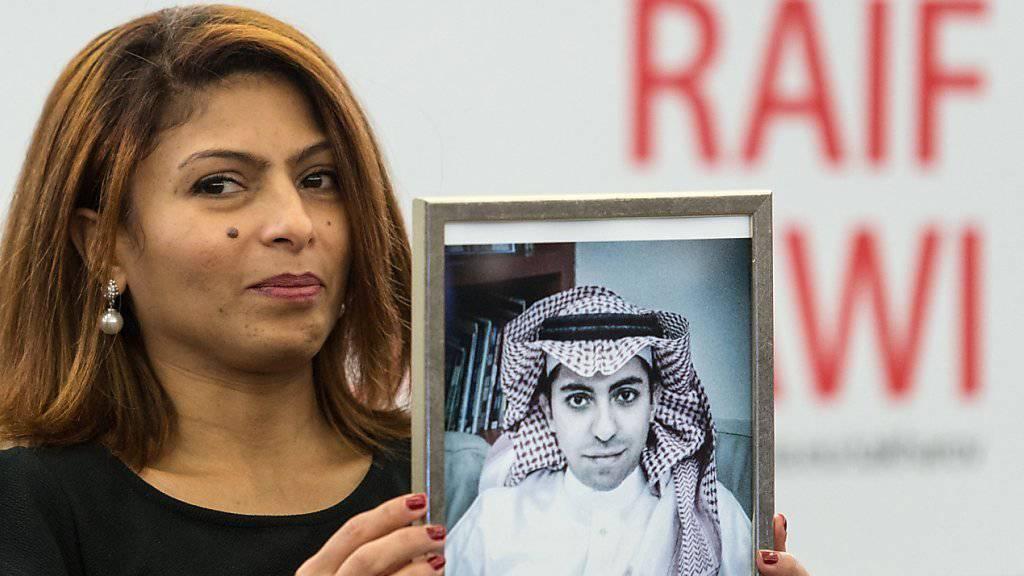Ein Bild vom inhaftierten saudischen Blogger Raif Badawi, hochgehalten von dessen Frau. Badawis Schwester wurde am Mittwoch in Polizeigewahrsam genommen. (Archiv)