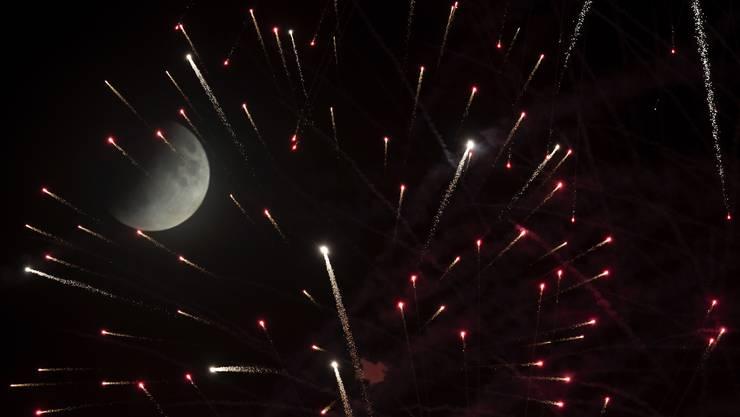 Die partielle Mondfinsternis aufgenommen mit Feuerwerk am Brezel-Festival in Speyer, Deutschland.