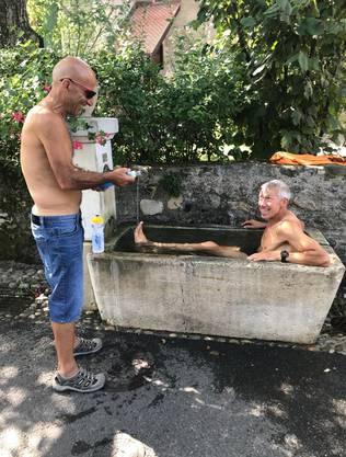 Roland Gröflin kühlt sich im Brunnen ab und scherzt mit seinem Tour-Betreuer Mosh Mangha.
